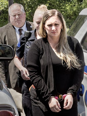 In a Friday July 13, 2018 photo, Samantha Jones, 30, is led into Magisterial Judge Jean Seaman's District Court in Warwick Township, Pa.,for her arraignment on homicide charges of killing her 11-month-old son through her drug-laced breast milk. (Kim Weimer/Bucks County Courier Times via AP)