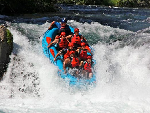 A group of rafters drops down Husum Falls on the White Salmon River.
