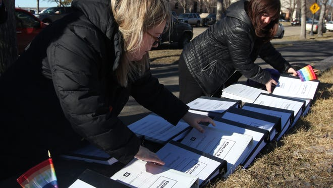 Representatives from American Civil Liberties Union of South Dakota, LGBT supporters and members of the Human Rights Campaign take binders of more than 80,000 signatures to Daugaard at the State Capitol in Pierre pushing him to veto the HB 1008 bill on Tuesday.