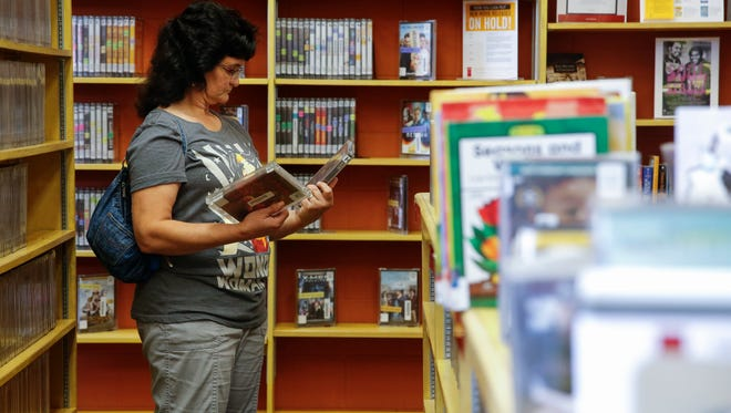 Donna Scott, of Elmwood Place, looks through scary movie DVDs, Friday, July 21, 2017, at the Elmwood Place branch of the public library.