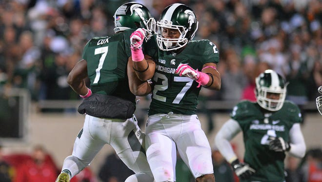 MSU's Demetrious Cox, left, and Khari Willis, right, celebrate after Cox broke up a fourth-down pass against Indiana on Oct. 24.