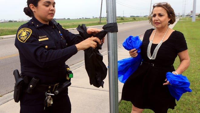 Lt. Emily Perez (left) and Principal Belinda Gamez tie ribbons on a pole in honor of former Police Chief Floyd Simpson Thursday May 7, 2015 at West Oso Elementary School in Corpus Christi. Gamez is on paid administrative leave after a student accused her of assault.