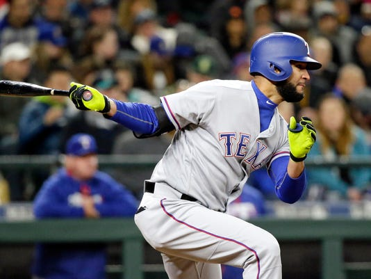 Texas Rangers' Nomar Mazara singles in a run against the Seattle Mariners during the sixth inning of a baseball game Friday, April 14, 2017, in Seattle. (AP Photo/Elaine Thompson)