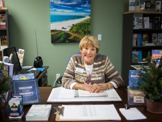 Mary Lou Connone sits at the desk where she greets customers in the visitor center of the Greater Naples Chamber of Commerce, where she has volunteered for more than 25 consecutive years, on Wednesday, Dec. 13, 2017.