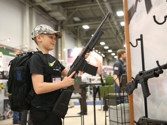 Blaise Maliskey, age 11, tries out a firearm in an