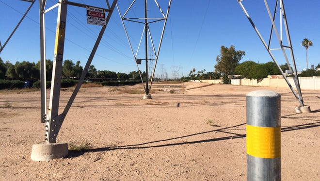 A barren stretch of dirt and weeds runs beneath several power-line towers just north of University Drive at Gilbert Road in central Mesa.