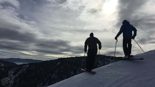 A pair of skiers pause to take in a view of Lake Tahoe during a morning run at Squaw Valley Resort.