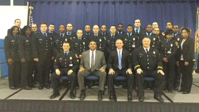 Delaware DOC 211th academy graduates with Deputy Commissioner Perry Phelps and Commissioner Robert M. Coupe seated in the front row wearing suits. (Phelps on the left, Couple on the right.)