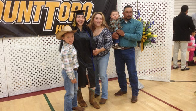 A Mount Toro High School graduate and her family pose for photos following Thursday's commencement held at the Boys & Girls Club in Salinas.