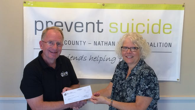 Jeff Ottum of the Door County Community Foundation gives a check to Cheryl Wilson of Prevent Suicide Door County.