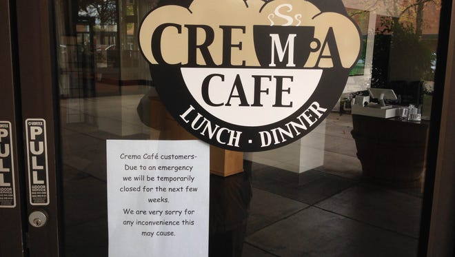 A sign posted on the door of Crema Café indicates the restaurant is temporarily closed due to an emergency.