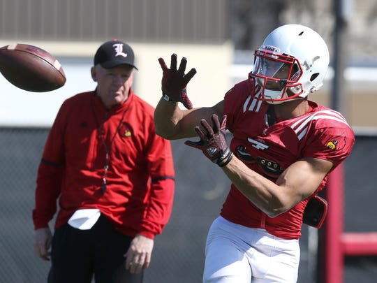 U of L football's Reggie Bonnafon, #7, catches a pass during practice as Coach Bobby Petrino looks on in the background.Mar. 29, 2016
