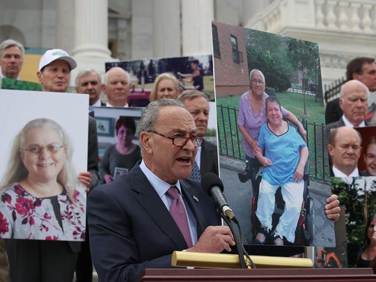 Minority Leader Chuck Schumer speaks while flanked by Senate Democrats holding photos of people who would lose their coverage under the Senate GOP health care bill during a press conference on June 27, 2017.