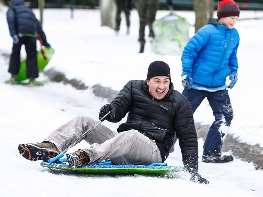 Sledders enjoying the sleet and snow that hit the Memphis area Friday, as they slide down an icy road inside Overton Park.