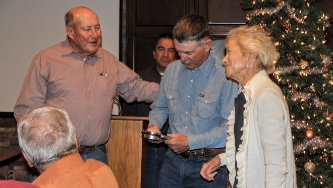 Otero County Soil & Water Conservation District Chairman Bill Mershon gives the 2016 Land Stewardship Award to Three Rivers Cattle Ltd. Co. Wednesday as part of their annual awards program.
