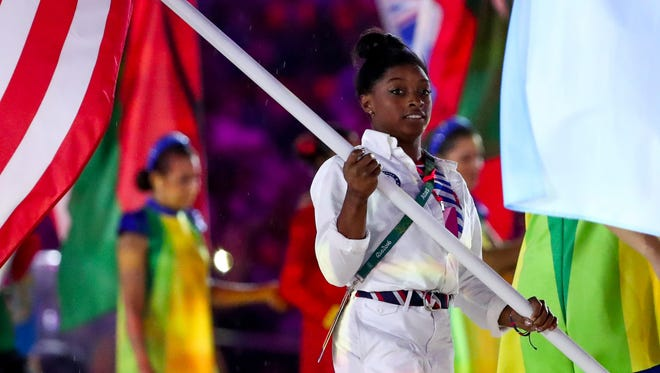 Simone Biles (USA) carries the flag during the closing ceremonies for the Rio 2016 Summer Olympic Games at Maracana.