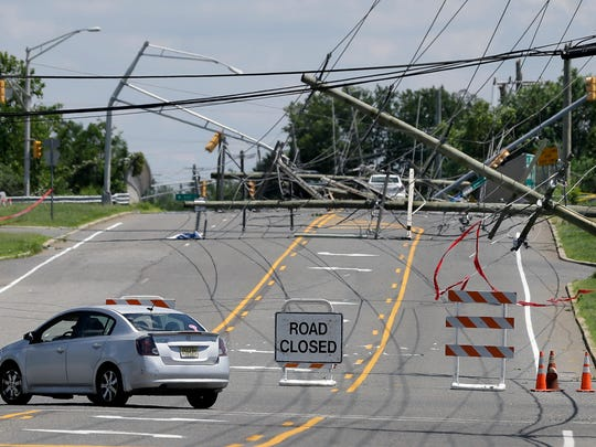 A driver turns her car at a closed road Wednesday after a violent storm downed poles and power lines Tuesday night in Gibbstown. Gloucester, Camden, Burlington and Salem counties saw the most damage from the ferocious storms that barreled through the region Tuesday night. (AP Photo/Mel Evans)