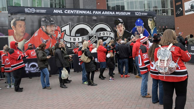 New Jersey Devils fans wait in line to see the NHL centennial fan arena museum before an NHL hockey game against the Dallas Stars Sunday, Mar. 26, 2017, in Newark, N.J. (AP Photo/Bill Kostroun)