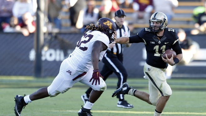 Purdue quarterback David Blough tries to avoid a sack against Minnesota.
