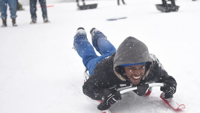 Antonio McKissack sleds down a hill at Shelby Park Golf Course during the snow storm Friday in Nashville.