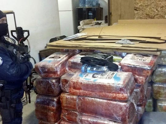 Below, a Federal Police officer guards packages that presumably contain tons of marijuana, next to a tunnel acces that was reportedly used for trafficking drugs.