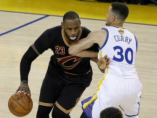 Cleveland Cavaliers forward LeBron James (23) dribbles against Golden State Warriors guard Stephen Curry (30) during the second half of Game 5 of basketball's NBA Finals in Oakland, Calif., Monday, June 13, 2016. (AP Photo/Marcio Jose Sanchez)