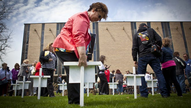 Cindy Menard pulls up a cross with the name of her daughter, Traci Sheibal, during the Workers Memorial Day ceremony April 26, 2013, at Iowa Workforce Development in Des Moines.