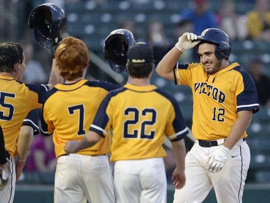 Victor's Chris Varone, right, is greeted at the plate by teammates after his two-run home run during a Class AA sectional semifinal at Frontier Field, Thursday, May 24, 2018.