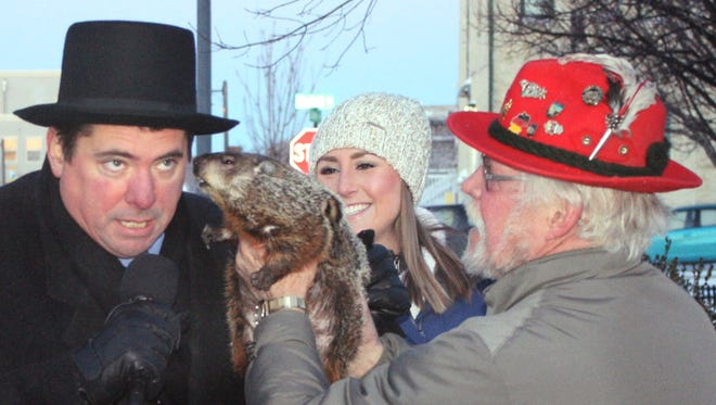Sun Prairie Mayor Jonathan Freund, left, leans in for Jimmy's prognostication just before being bitten on ear by the groundhog during the Groundhog Day celebration on Feb. 2.