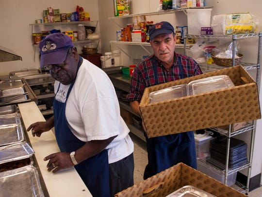 Fazel Jigry, right, and Norman Strother, left, help set out food at the Valley Mission for a breakfast hosted by The News Leader as part of Make a Difference Day in Staunton on Saturday, Oct. 25, 2014.