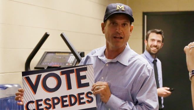 Michigan football coach Jim Harbaugh holds a sign for Detroit Tigers leftfielder Yoenis Cespedes on June 30, 2015, in Detroit.