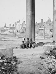 In this April 1865 photo provided by the Library of Congress, as seen through the porch of the Circular Church, people sit amongst ruined buildings in Charleston, S.C. On Nov. 16, 1864, Gen. William T. Sherman watched his army pull out of Atlanta, and marched with 62,000 veteran troops to the Atlantic coast at Savannah, conquering territory and making a point to the enemy in what would be known as Sherman's March to the Sea. In South Carolina, his worst destruction left the capital, Columbia, a wasteland.