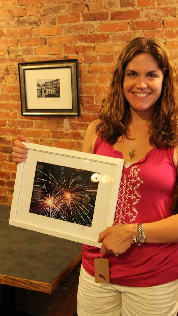 Brockport photographer Courtney Webster hanging her show at Java Junction. photo by Caurie Putnam