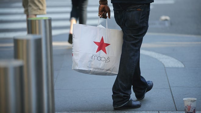 FILE - JANUARY 8, 2014: It was reported that Macy's plans to lay off about 2,500 employees and close five stores as part of a restructuring plan January 8, 2014. CHICAGO, IL - AUGUST 14:  A shopper carries a purchase from Macy's along the Magnificent Mile shopping district on August 14, 2013 in Chicago, Illinois. Macys reported lower than-expected second quarter sales today and cut their profit outlook for the year. Some analysts fear the disappointed news will reverberate throughout the retail sector because Macy's is looked at as a barometer of spending among middle- to upper-income shoppers.  (Photo by Scott Olson/Getty Images) ORG XMIT: 176710015 ORIG FILE ID: 176518942