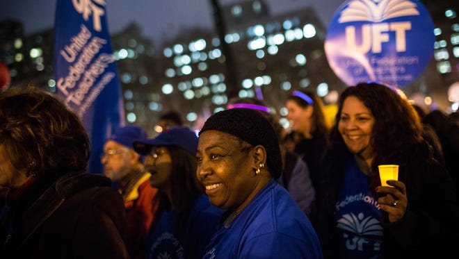 A woman attends a rally calling on greater social equality, organized by non-unionized fast food workers demanding for a wage raise from $7.25 per hour to $15.00 per hour and to be unionized on Dec. 5, 2013, in New York.  The day held various protests in front of fast food outlets around the country and culminated in a larger rally attended by various social groups, unions and organizations in downtown Manhattan.