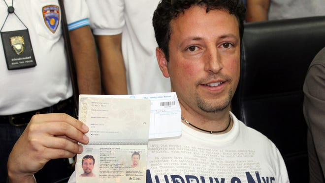 Italian Luigi Maraldi, whose stolen passport was used by a passenger boarding a missing Malaysian airliner, shows his passport as he reports to Thai police Sunday at Phuket police station in Phuket province, southern Thailand.  Maraldi showed his current passport, which replaced the stolen one, and expressed surprise that anyone could use his old one.