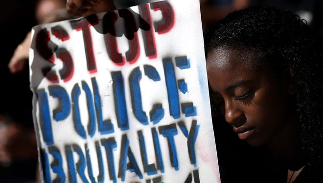 A demonstrator in Oakland, Calif., marks a moment of silence in solidarity with victims of police brutality Thursday.