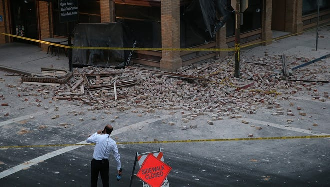 A reporter surveys the scene of a building collapse following a 6.0 earthquake on Aug. 24, 2014 in Napa, Calif.