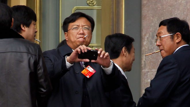 Chinese delegates attending a meeting at the Great Hall of the People smoke cigarettes in Beijing, China.