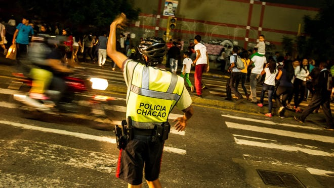A policeman controls traffic in Caracas, Venezuela, on Monday during a blackout.