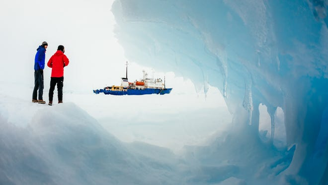 Passengers from the Russian ship MV Akademik Shokalskiy, trapped in the ice 1,500 nautical miles south of Hobart, Australia, walk around the ice.
