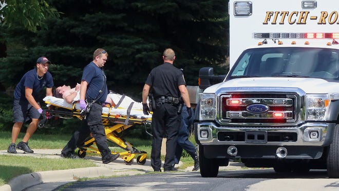 Emergency personnel transport Andy Steele on Friday, Aug. 22, 2014, from his home in Fitchburg, where authorities said Steele's wife, Ashlee Steele, and sister-in-law, Kacee Tollesfsbol, were found shot dead.