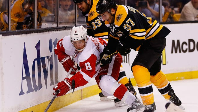 Justin Abdelkader of the Detroit Red Wings reaches for the puck as Patrice Bergeron (37) and Zdeno Chara (33) of the Boston Bruins defend in the first period in Game 1 of their playoff series.