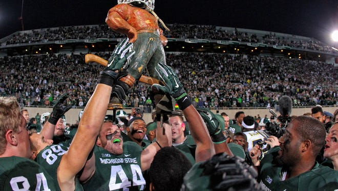 Michigan State Spartans defensive end Marcus Rush (44) holds up Paul Bunyan trophy  after a game at Spartan Stadium.