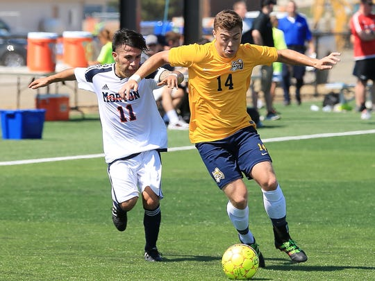 Ocelots defender Alex DeFlorio (No. 14) of Livonia Stevenson outpaces Morton College's Jose Garcia. The game Friday was the first-ever on Schoolcraft's turf field.