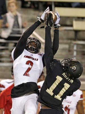 Louisville's Jamari Staples (2) catches a pass over Wake Forest's Dionte Austin (11) in the first half of an NCAA college football game in Winston-Salem, N.C., Friday, Oct. 30, 2015. (AP Photo/Chuck Burton)