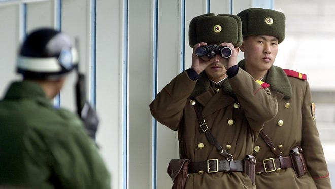 A North Korean soldier looks to the South through binoculars at Panmunjom in the demilitarized zone (DMZ) between North and South Korea, 26 February 2003 while a South Korean soldier talks on a radio.