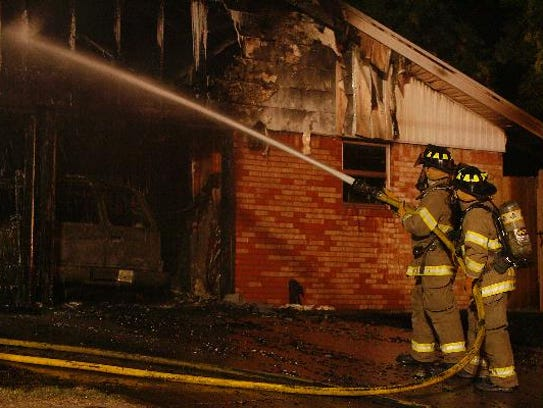 A San Angelo firefighters hose down a structure fire.