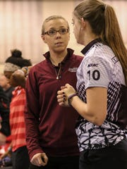 Head Coach Kayla Bandy speaks with junior Melanie Copey at a Hawks tournament.