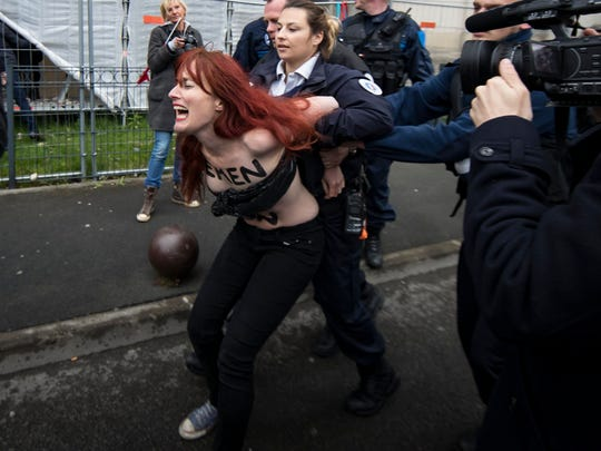 A FEMEN activist is arrested after protesting a few